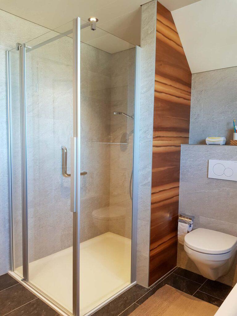 Wooddesign_Badmöbel_ Badumbau_Nussbaum furniert_weisse Fronten_Kunstharzabdeckung_Waschbecken eingelassen-Duschtrennwand-LED-Beleuchtung (3)