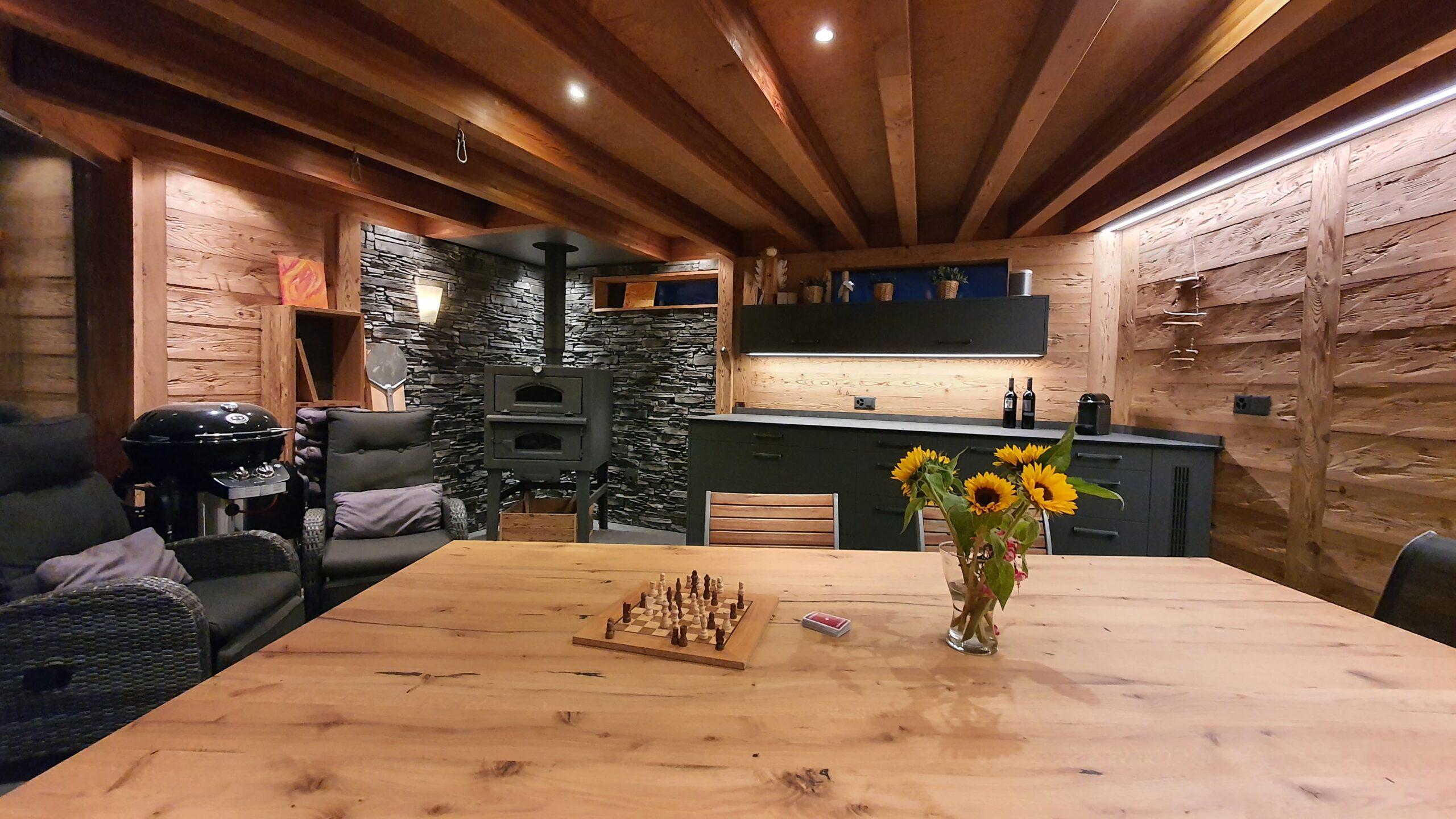 Wooddesign_Holzdesign_Pergola_Outdoor-Küche_Altholz_modern_rustikal_Pizzaofen_Steinwand_LED-Beleuchtung_Outdoor-Sessel_Esstisch (4)