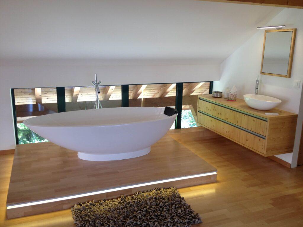 Wooddesign_Holzdesign_Plasselb_Loftwohnung_offennes Schlafzimmer und Bad_freistehende Badewanne_Parkett_ Ankleide_WC (1)-min