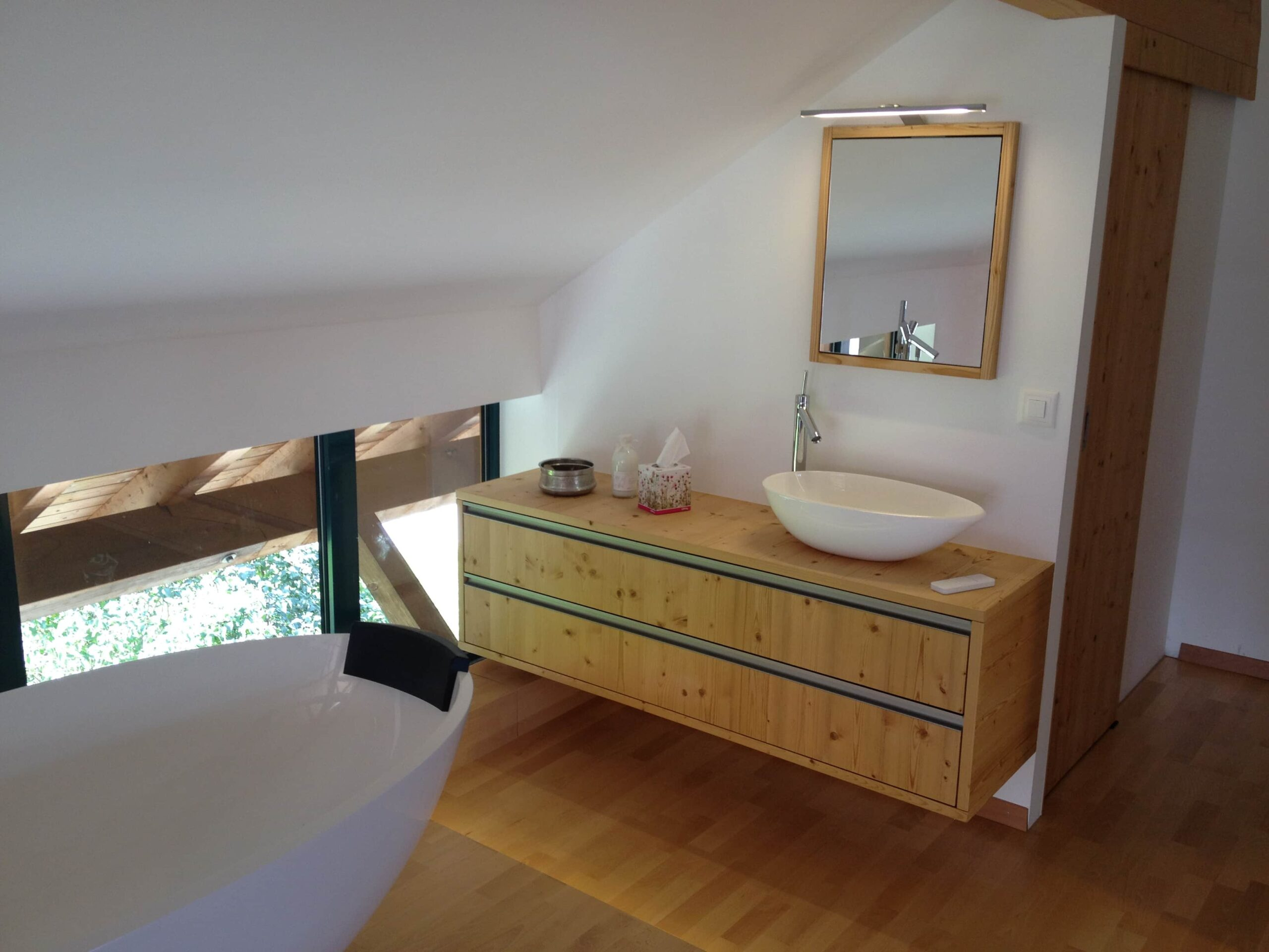 Wooddesign_Holzdesign_Plasselb_Loftwohnung_offennes Schlafzimmer und Bad_freistehende Badewanne_Parkett_ Ankleide_WC (8)-min